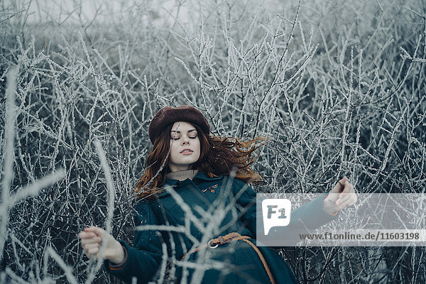 Caucasian woman laying on branches in winter field
