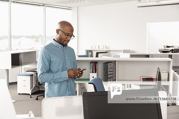 African American man texting on cell phone in office