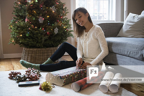 Mixed Race woman wrapping gift on floor near Christmas tree