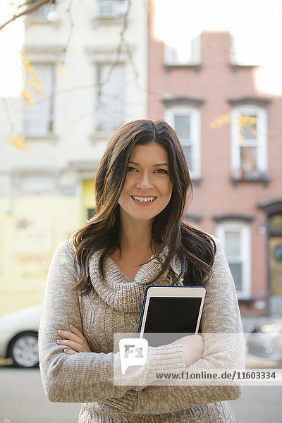 Caucasian woman holding digital tablet in city