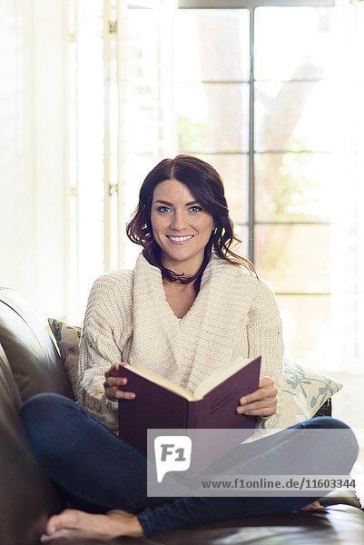 Caucasian woman sitting on sofa reading book