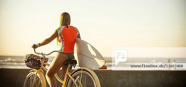 Caucasian teenage girl carrying surfboard on bicycle