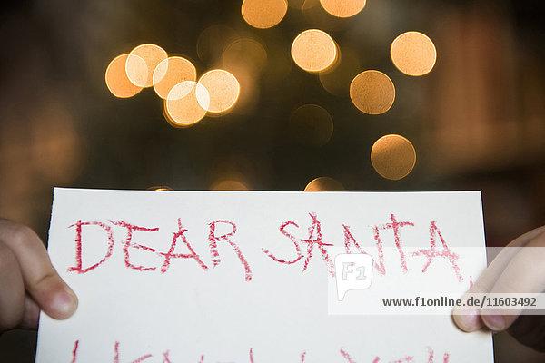 Hands of Caucasian girl holding dear Santa letter