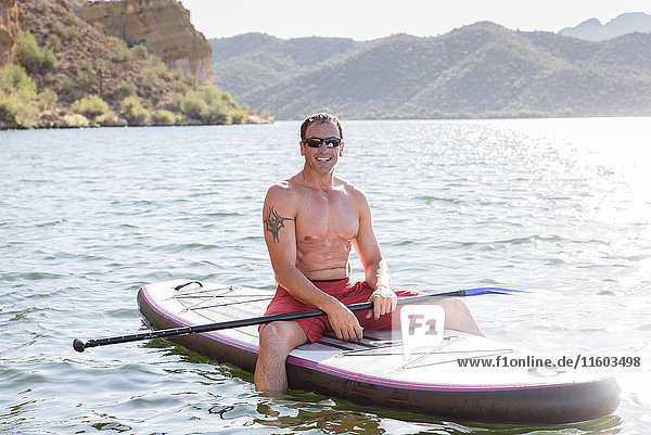 Hispanic man sitting on paddleboard in river
