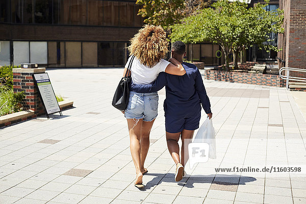 Black women walking and hugging in city