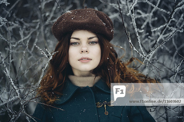 Serious Caucasian woman near icy branches