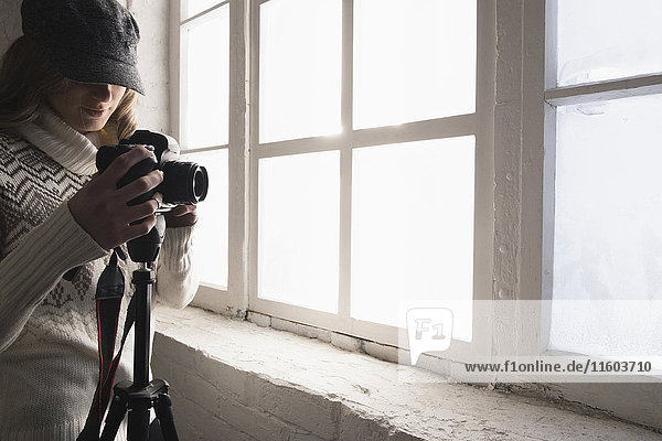 Caucasian woman near window photographing with camera