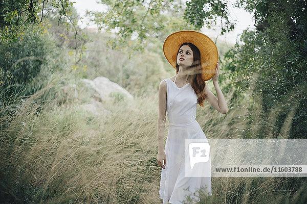 Caucasian woman wearing hat walking in tall grass