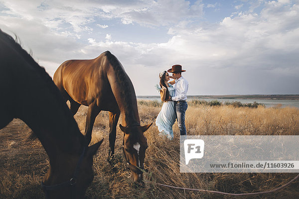 Horses grazing near Caucasian woman hugging cowboy