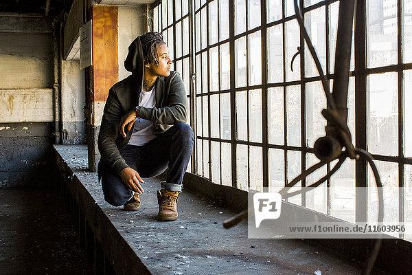 Androgynous Mixed Race woman crouching near window