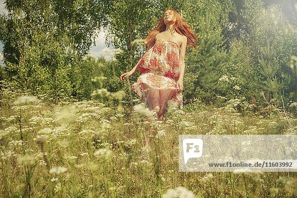 Caucasian woman twirling in field of wildflowers