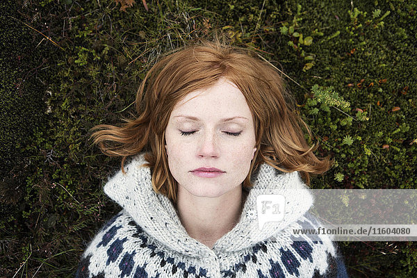 Caucasian woman laying on moss with eyes closed