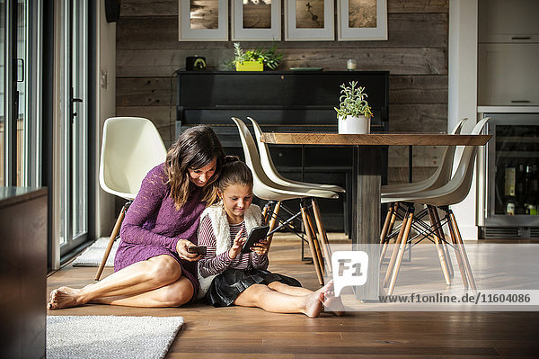 Smiling mother and daughter sitting on floor texting on cell phones