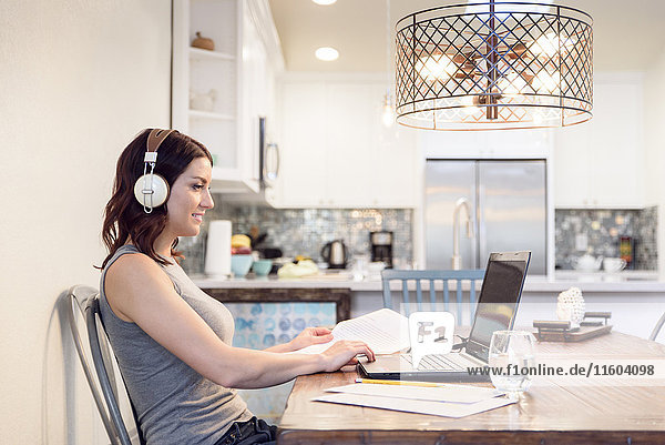 Caucasian woman listening to headphones reading paperwork using laptop