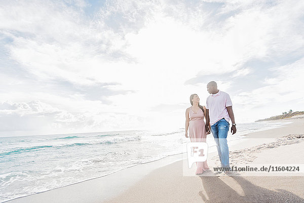 Couple holding hands walking on beach