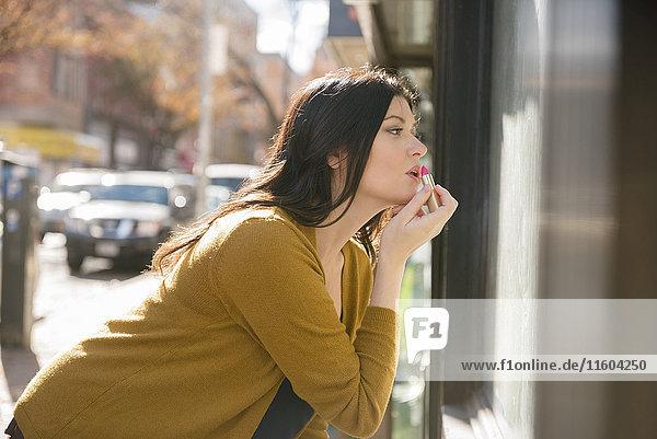 Caucasian woman applying lipstick in city