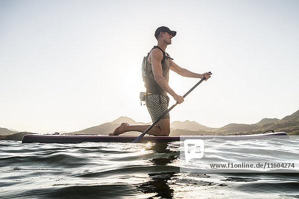 Caucasian man kneeling on paddleboard in river