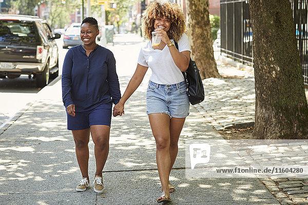 Black women holding hands on city sidewalk