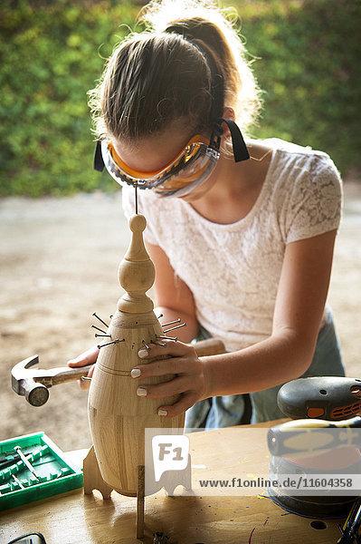 Caucasian girl hammering nails into birdhouse