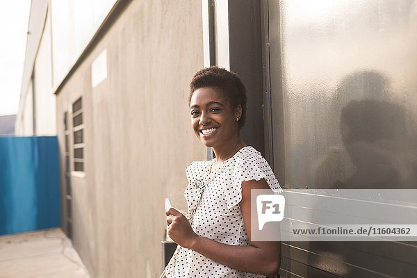 Smiling African American woman holding cell phone