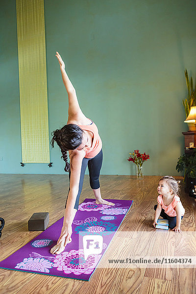Mixed Race expectant mother practicing yoga and watching daughter