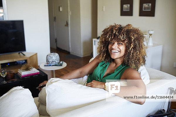 Portrait of smiling Black woman sitting on sofa