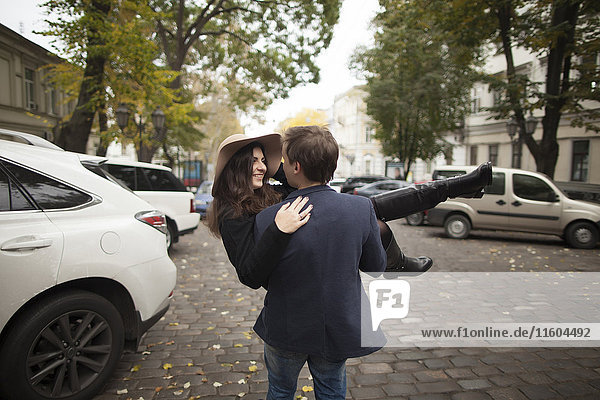 Caucasian man carrying woman on cobblestone street