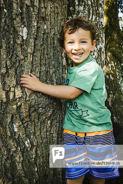 Portrait of smiling Caucasian boy hugging tree