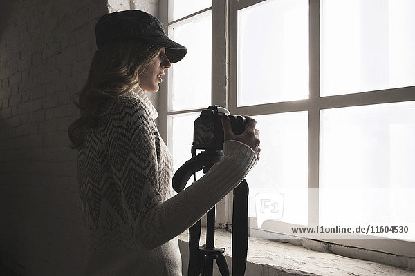 Caucasian woman near window holding camera
