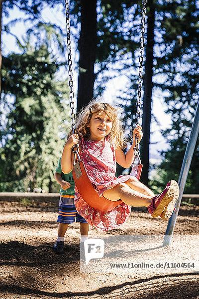 Caucasian boy pushing sister on playground swing