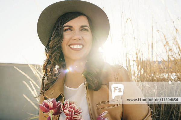 Portrait of smiling Mixed Race woman wearing hat holding flowers