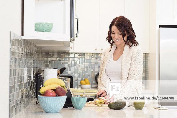 Caucasian woman cutting fruit in domestic kitchen