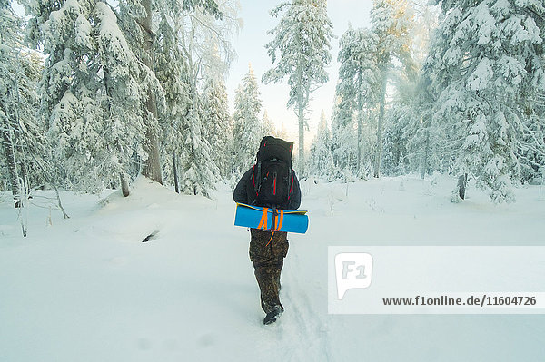 Caucasian man hiking in snowy forest