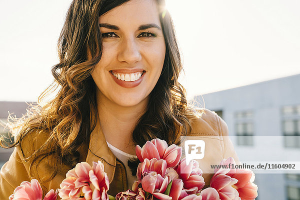 Portrait of smiling Mixed Race woman holding flowers