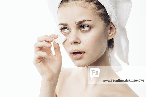 Caucasian woman cleaning eye with pad