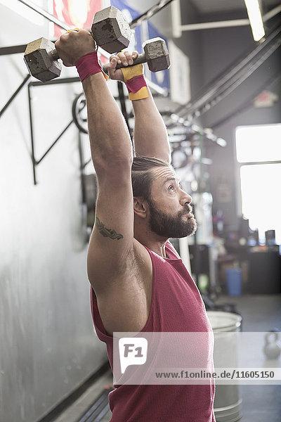Mixed Race man lifting dumbbells in gymnasium