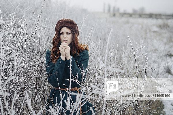 Caucasian woman rubbing hands in winter field
