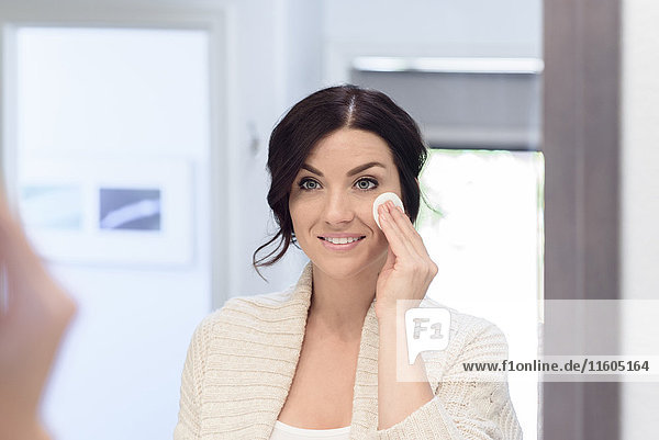 Caucasian woman cleaning face with pad in mirror