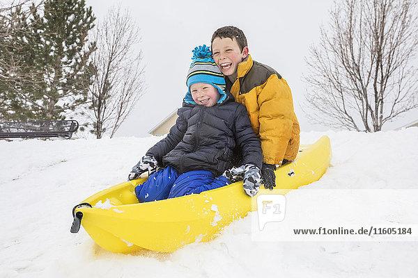 Smiling boys sliding on toboggan on hill in winter