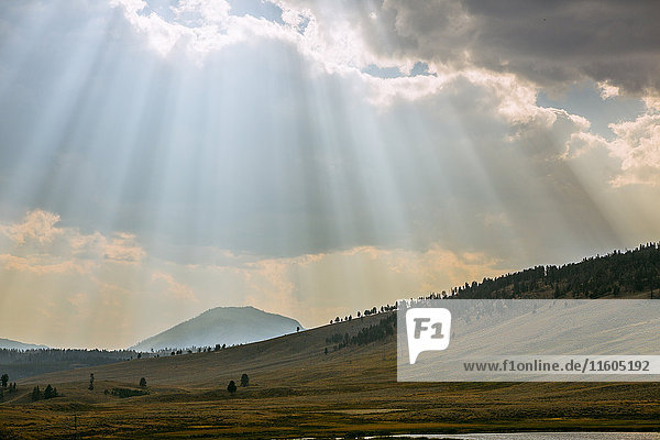Sunbeams shining through clouds over rolling rural landscape