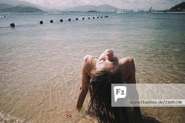 Caucasian woman wearing bikini sitting in waves on beach