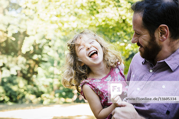 Caucasian father carrying laughing  daughter