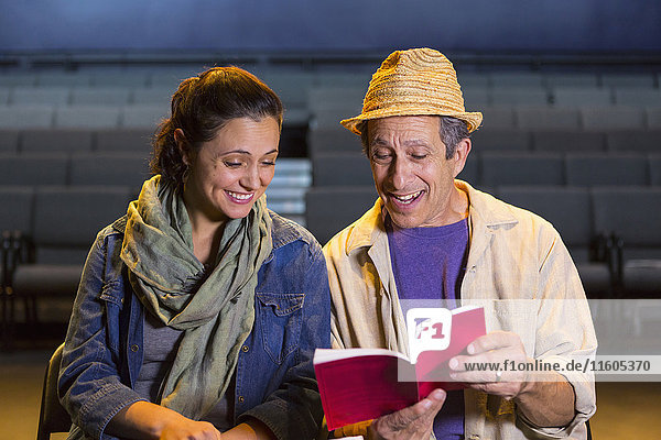 Caucasian actors rehearsing with script in theater