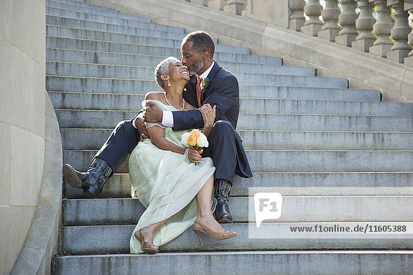 Black couple kissing on stone staircase