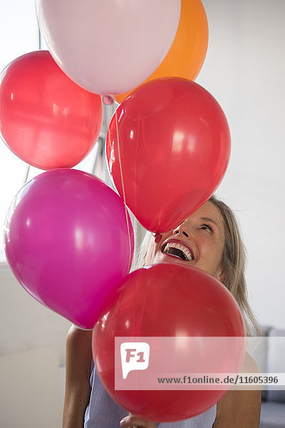 Smiling Caucasian woman holding multicolor helium balloons