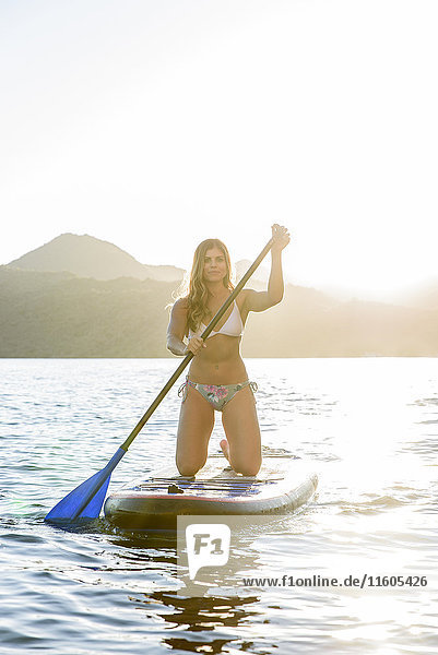 Hispanic woman kneeling on paddleboard in river