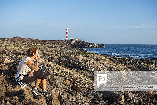 Caucasian woman sitting on rocks at ocean
