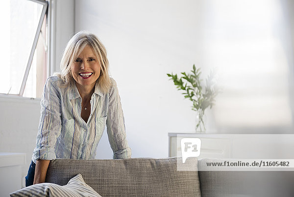 Smiling Caucasian woman leaning on sofa