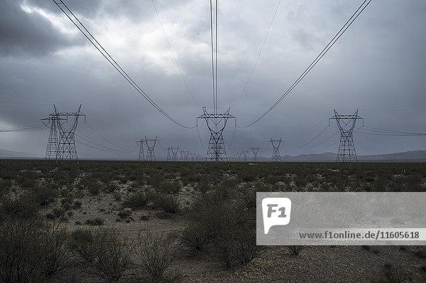 Strommasten und Anlagen im Feld gegen bewölkten Himmel Strommasten und Anlagen im Feld gegen bewölkten Himmel