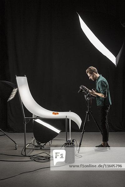 Seitenansicht des Fotografen beim Fotografieren von Lebensmitteln im Studio